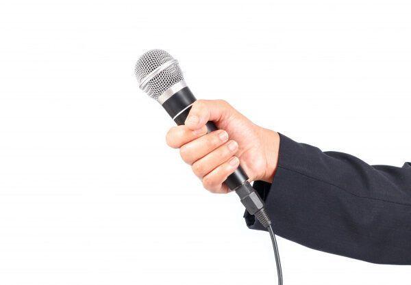 Рука, которая держит микрофон